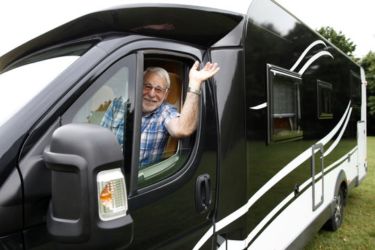 Rentner am Steuer  winkt aus seinem Wohnmobil