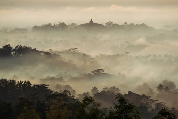 Colorful sunrise over Borobudur temple in misty jungle forest, I