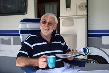Lachender Rentner sitzt vor seinem Wohnwagen beim Campingurlaub
