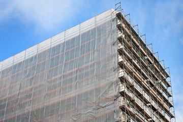 Staircase and scaffolding on a construction site,covered with mesh on sky background