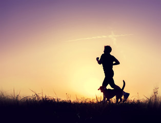 Runner with dog silhouettes at the sunset