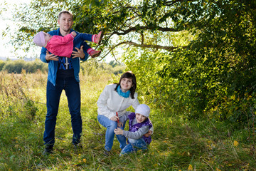 Family resting the meadow in autumn