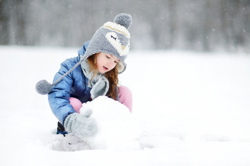 Funny little girl having fun in winter park
