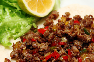Roasted minced beef with chili pepper on tortilla with lettuce and lemon