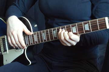 Musician in black on a black six strings electric guitar playing. Hands of the musician close up