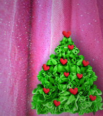 Christmas tree decorated red hearts on pink background