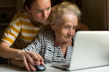 Young girl teaches her grandmother to work on the computer.