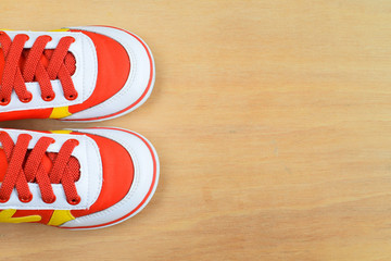 Picture of a pair of kids sport shoes on wood board
