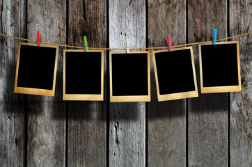 Old picture frame hanging on clothesline on wood background.