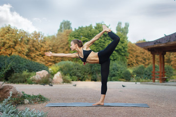 Good morning with yoga.Beautiful young caucasian woman in fitness wear doing exercises in a park