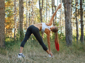 Warming-up. Beautiful young caucasian woman in fitness wear doing exercises in a park