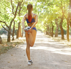 Beautiful young caucasian woman in fitness wear doing exercises in a park