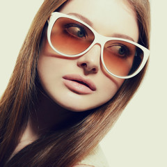 Beautiful young model with big sunglasses, close up, image toned
