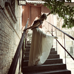 Romantic image of young beautiful girl ballet dancer posing on s