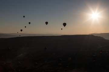 Several Ballons flying over cappadocia in front of the rising sun