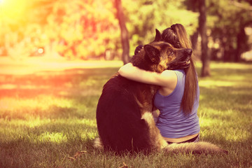 Beautiful young girl with dog in park