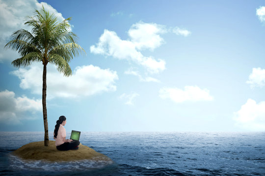 Business woman working with laptop on the small island