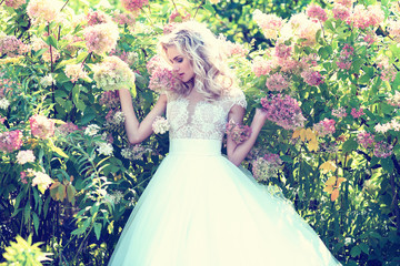 Beautiful bride posing outdoor. Wedding dress, curly blond hair.