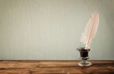 photo of white Feather and inkwell on old wooden table. retro filtered image
