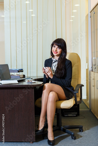 pretty woman in a short skirt drinking coffee in the office stock photo and royalty free. Black Bedroom Furniture Sets. Home Design Ideas