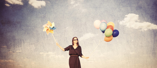 girl in black dress with multicolored balloons