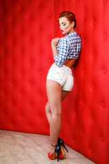 Sexy retro pin up girl in short shorts, isolated on red
