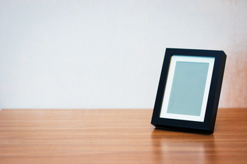 Blank black picture frame at the desk - vintage style effect picture