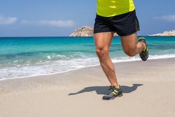 Young man running on a sandy beach.
