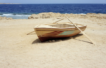 Lonely boat with oars in the coast