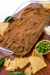 preparation of bean dip with jalapenos, sour cream and cheddar c