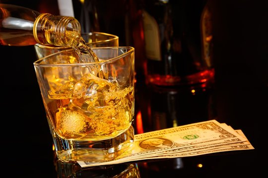 barman pouring whiskey in front of whisky glass and bottles near dollars