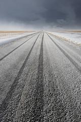 Strada innevata con tracce di pneumatici verticale