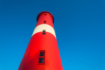 Shipping Lighthouse red and white markings against blue morning sky