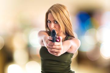 Military woman aiming a gun