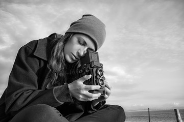 Lifestyle Portrait. Young Female Photographer Using Vintage Camera