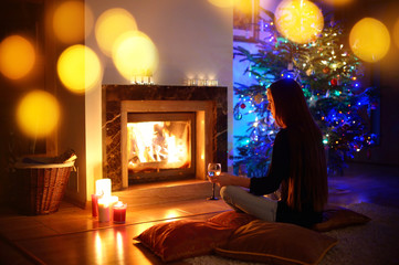 Woman having a drink by a fireplace in a on Christmas