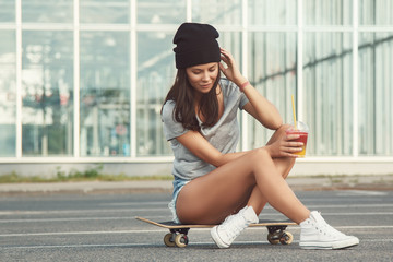 Beautiful woman sitting on skateboard