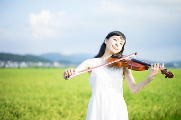 屋外でヴァイオリンを弾く女性