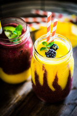 Colorful two layer smoothies with mango and berries on rustic wo