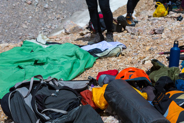 Hiking Gear Heap of Dropped in Mess Mountain Climbing and Camping Equipment Backpack Helmet Sleeping Bag Boots Thermos Flask and Other Legs of People Blurred Behind