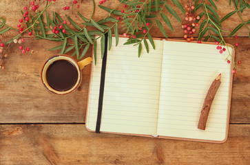 open blank vintage notebook and wooden pencil next to hot cup of coffe