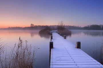 Boardwalk on a lake at dawn in winter, The Netherlands
