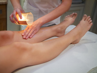 Woman getting spa massage with massage candle