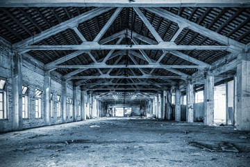 Empty industrial loft in an architectural background with bare cement walls, floors and pillars supporting a mezzanine blue tone
