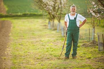 Portrait of a handsome senior man gardening in his garden, on a