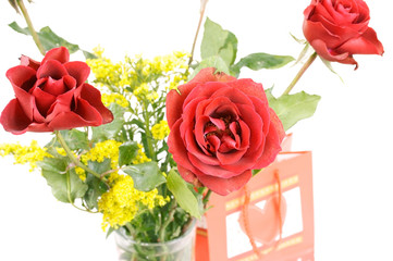 Bouquet of roses with present bag