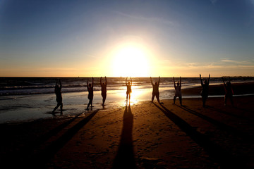 yoga in group as silhouette by the sea at sunset