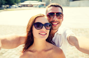 smiling couple wearing sunglasses making selfie