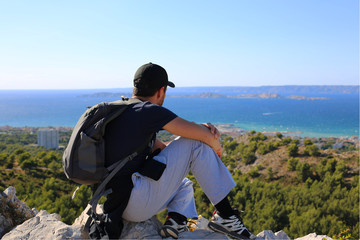 young man sitting on a summit and looking the sea