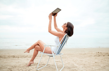 happy woman with tablet pc taking selfie on beach